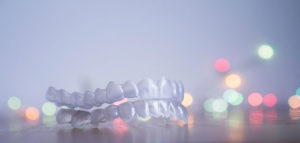 Clear-tooth-aligners-in-front-of-colorful-lights.